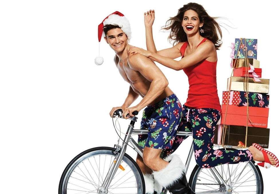 Guy and Girl on bike with Christmas presents from Peter Alexander