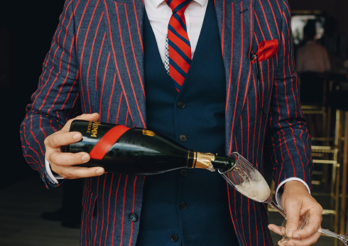man in a striped blazer pouring a glass of champagne